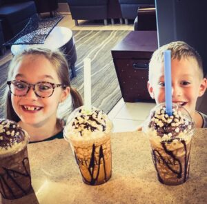Two children looking excitedly at sweet, chocolaty drinks