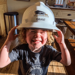Dr. Grant Olson's son with a too-big hard hat on
